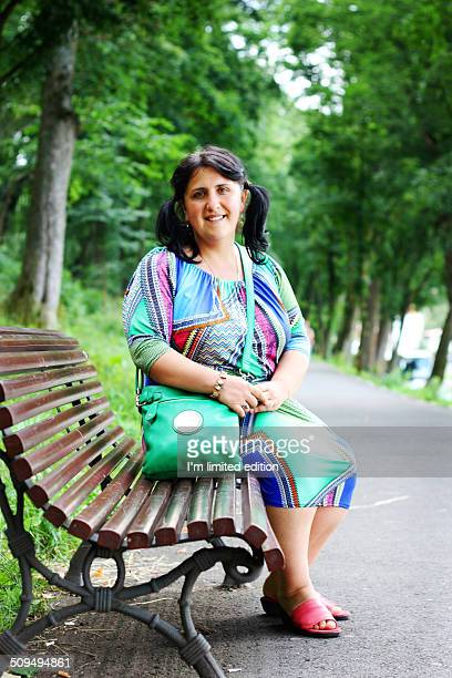 Overweight middle aged woman sitting on bench