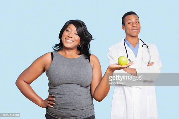 Overweight mixed race woman holding green apple with doctor over blue background