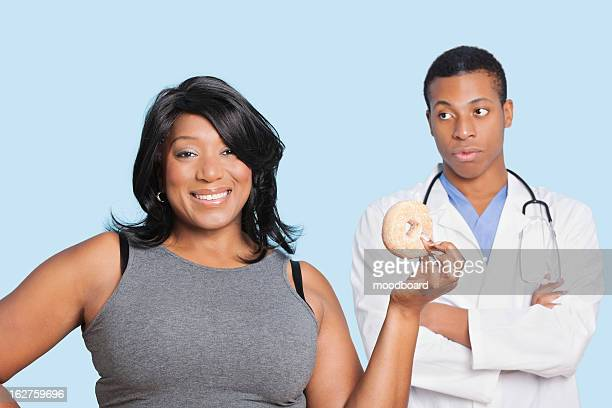 overweight mixed race woman with donut by doctor over blue background - fat people eating donuts stock pictures, royalty-free photos & images