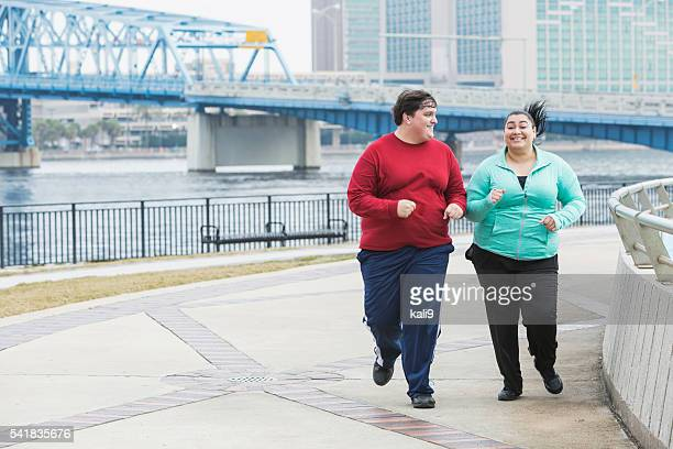 Overweight people exercising, running and smiling