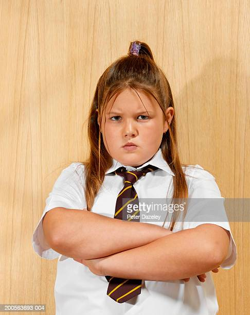 Overweight schoolgirl (8-9) standing with arms crossed, frowning