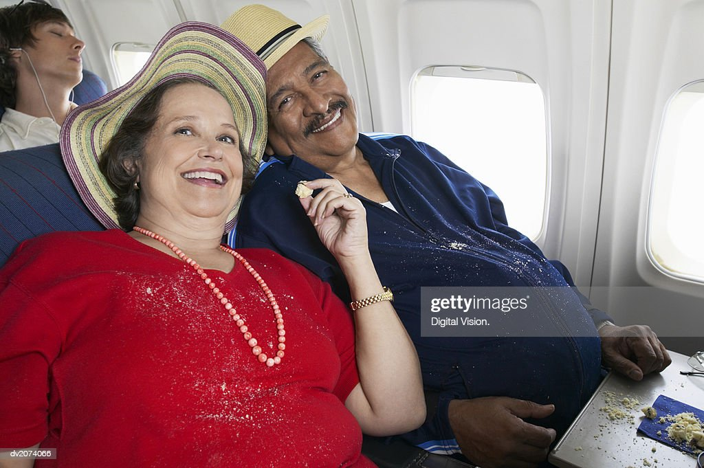 Overweight Senior Couple Sit on a Plane Sharing Cake, Crumbs on Their Clothes : Stock Photo