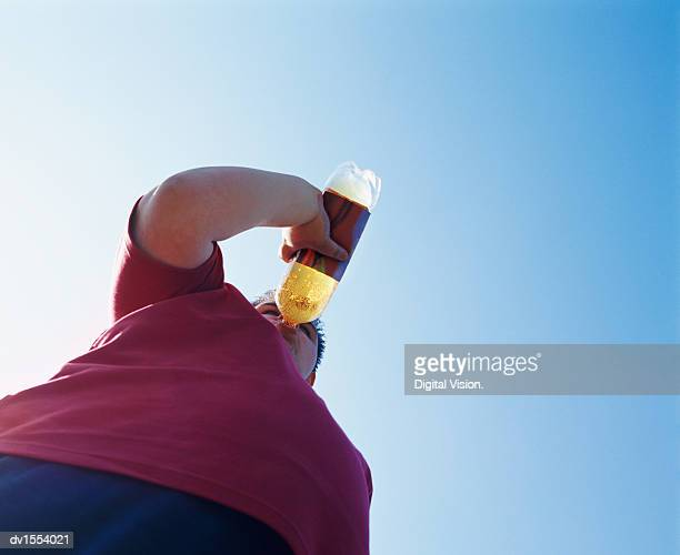 Overweight Teenage Man Drinking From a Bottle