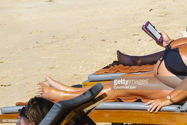 Overweight tourist woman on a deck chair reading in a kindle book reader on the beach on December 14 2016 in Thandwe Ngapali Beach Myanmar