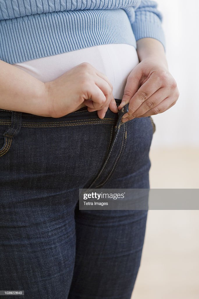Overweight woman buttoning up her jeans : Stock Photo