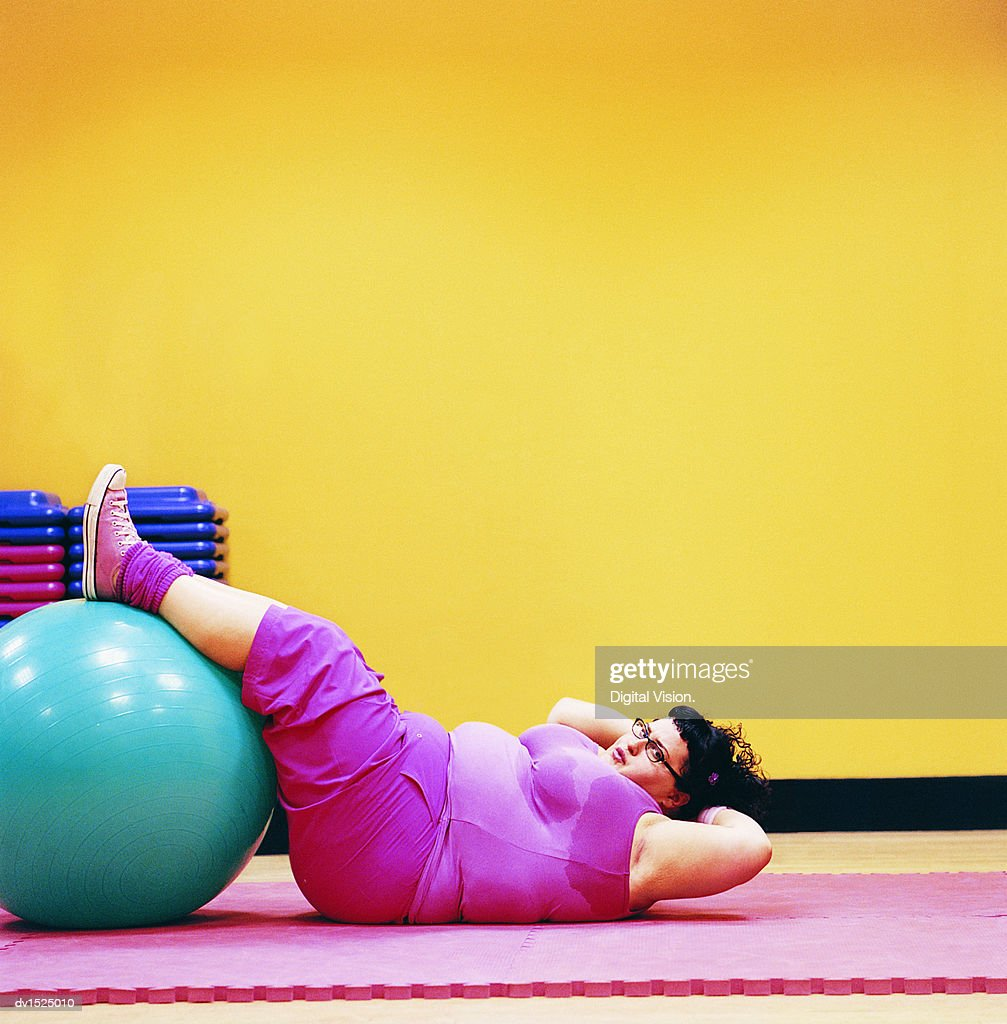 Overweight Woman Doing Sit Ups in a Gym With Her Feet Up on an Exercise Ball : Stock Photo