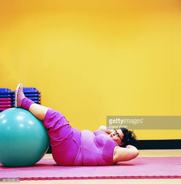 Overweight Woman Doing Sit Ups in a Gym With Her Feet Up on an Exercise Ball