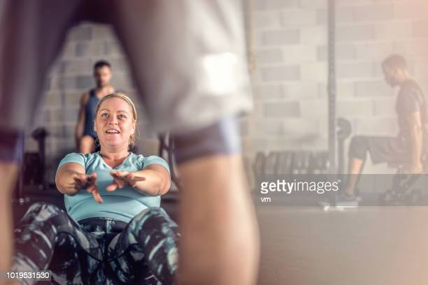 overweight woman doing sit-ups in the gym - fat woman sitting on man stock pictures, royalty-free photos & images