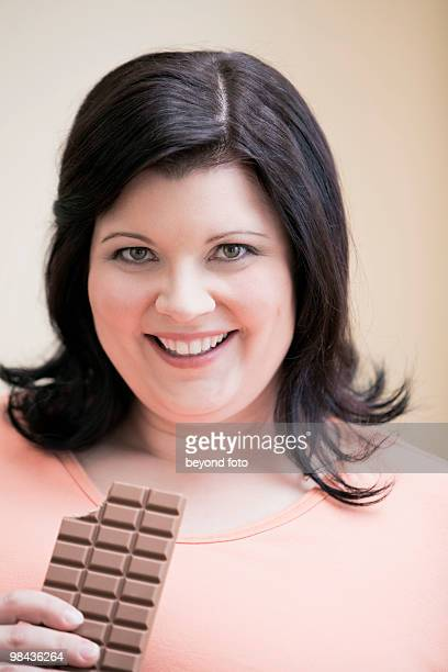 overweight woman eating chocolate bar