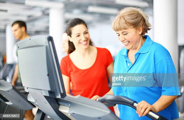 Overweight woman exercising on a treadmill with instructor.