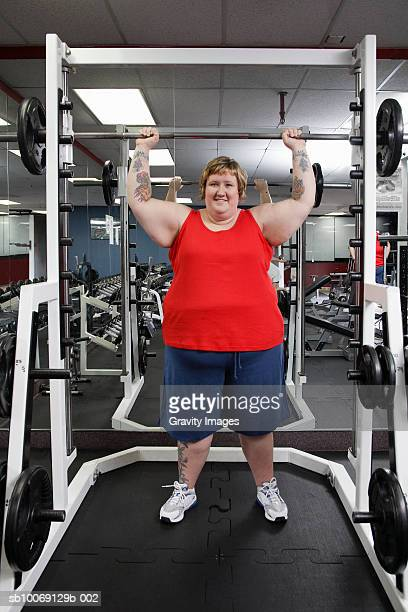 overweight woman exercising with barbell in gym, portrait - short hair for fat women stock pictures, royalty-free photos & images