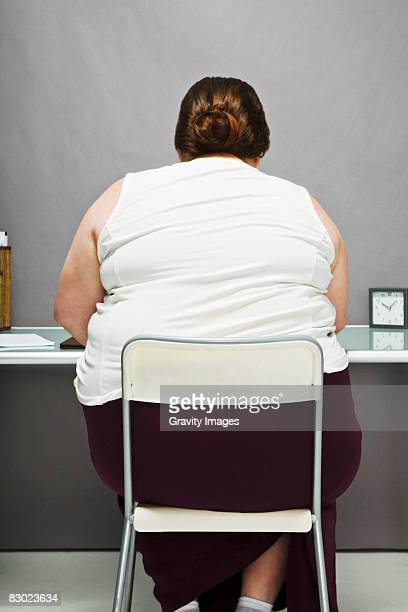 Overweight woman in chair, back view