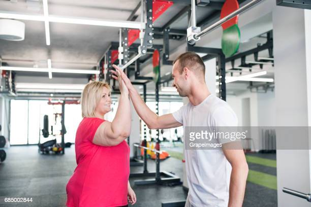 Overweight woman in gym giving high five to her personal trainer after working out.