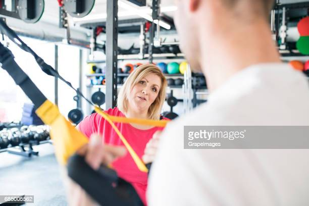 Overweight woman in gym training arms with trx fitness straps.