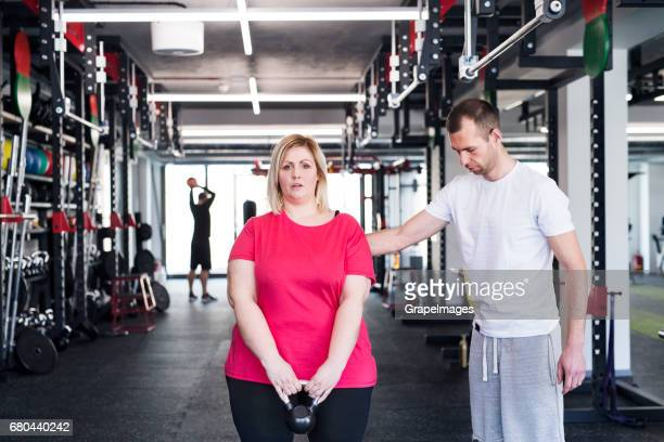 Overweight woman in gym working out with kettlebell.