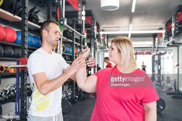 Übergewichtige Frau in Turnhalle der Ausarbeitung mit Kettlebell.
