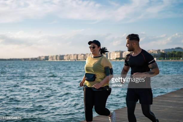 mujer con sobrepeso corriendo con entrenador - modelos gorditas fotografías e imágenes de stock