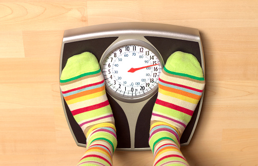 Overweight woman on bathroom scales - gettyimageskorea