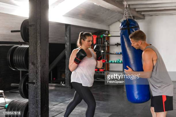 overweight woman punching a boxing bag with the help of her fitness instructor - leisure facilities stock pictures, royalty-free photos & images