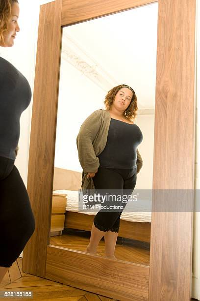overweight woman reflection in mirror - fat lady in leggings stock photos and pictures