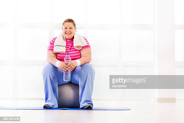 Overweight woman resting on fitness ball.