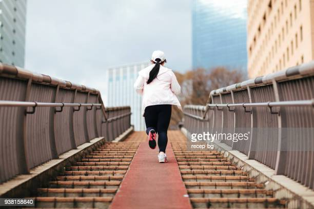 overweight woman running at stairs - fat asian woman stock pictures, royalty-free photos & images