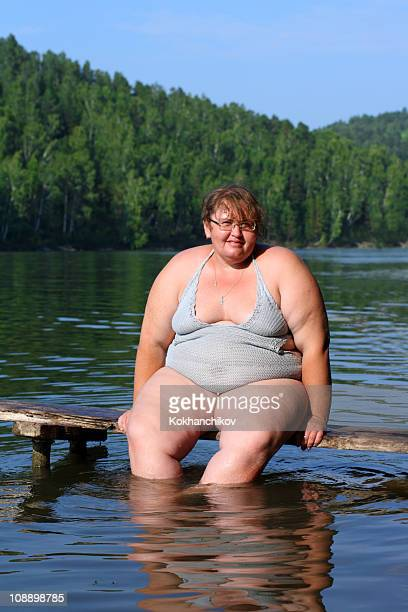 overweight woman sitting on stage - swimwear stock photos and pictures