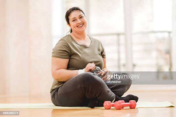 overweight woman taking a break from exercising. - chubby stock photos and pictures