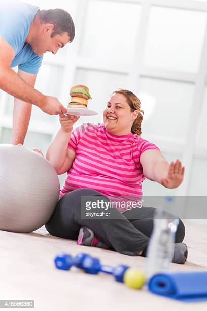 Overweight woman taking hamburger and refusing to exercise.