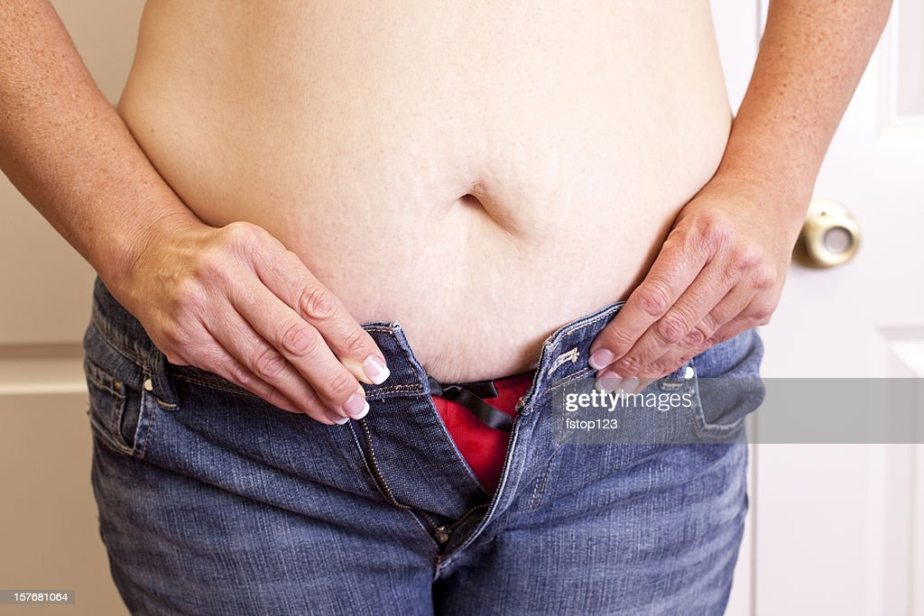Overweight woman trying to button her jeans. Too tight. Belly. : Stock Photo