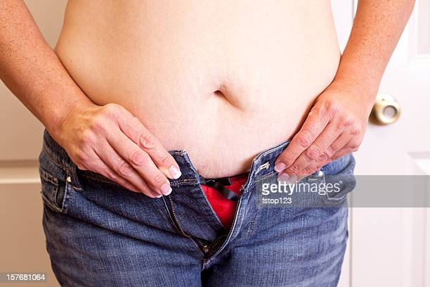 Overweight woman trying to button her jeans. Too tight. Belly.
