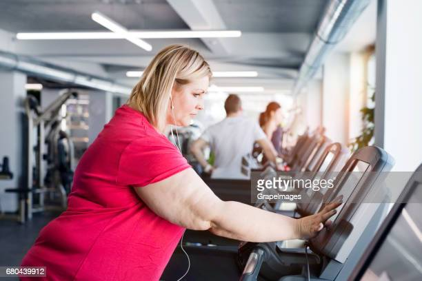 overweight woman walking on treadmill in modern gym. - fat blonde women stock photos and pictures