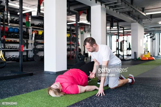 overweight woman with her personal trainer in modern gym. - big arse stock pictures, royalty-free photos & images