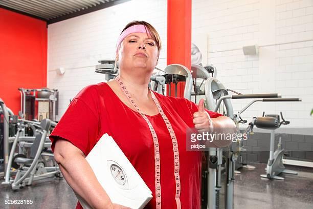 Übergewichtige Frau mit Waage, dem victory Blick im Fitnessraum