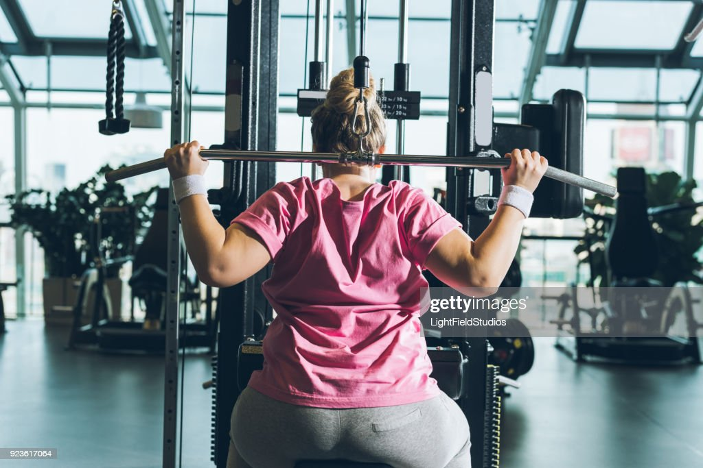 overweight woman working out on training apparatus : Stock Photo