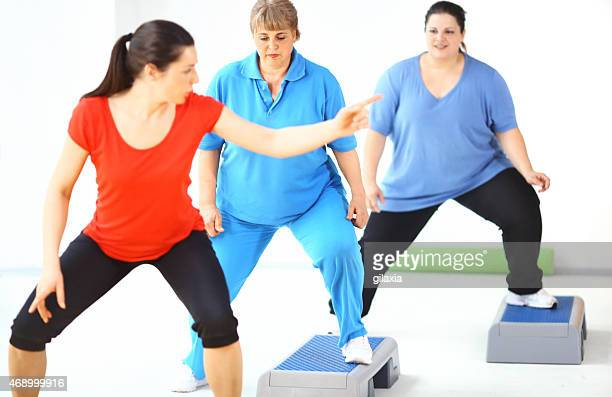 Overweight women exercising with instructor.