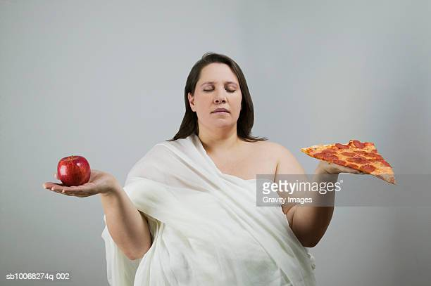 Overweight women holding apple and pizza, eyes closed, close-up