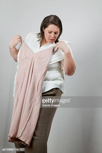 overweight women holding up small dress, looking down, close-up - jaded pictures stock photos and pictures