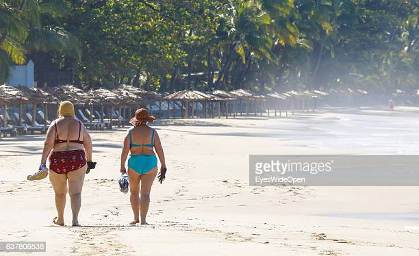 Overweight women in a bikini walking along the white sandy beach with palmtrees and blue sky on December 14 2016 in Thandwe Ngapali Beach Myanmar