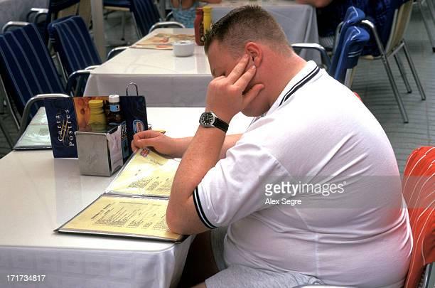 Overweight young British man reading restaurant menu