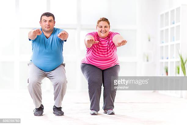 Overweight young couple doing squats and looking at the camera.