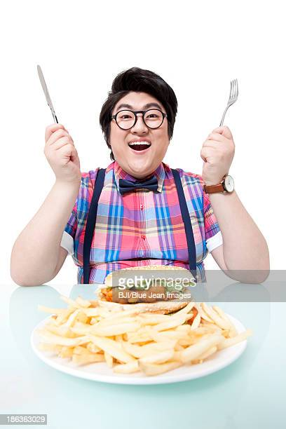 Overweight young man eating fast food