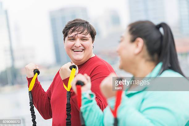 Overweight young man, friend exercising together