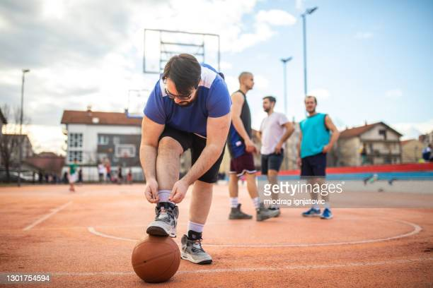 overweight young man tying shoelace before playing basketball with his friends - tying shoelace stock pictures, royalty-free photos & images