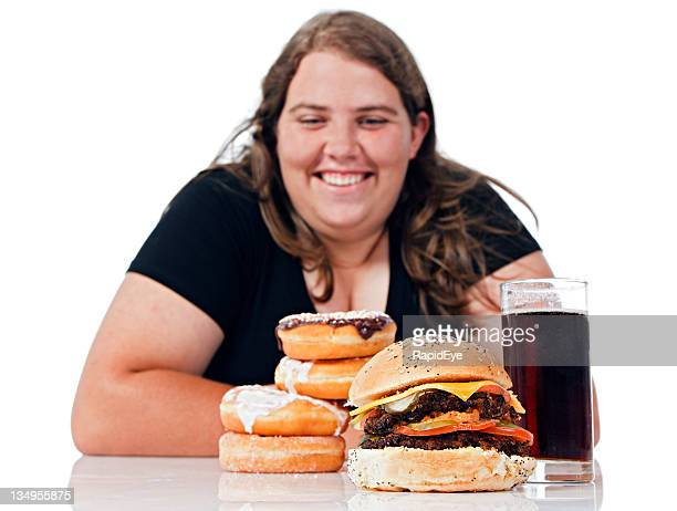 Overweight young woman smiles at  pile of fattening junk food
