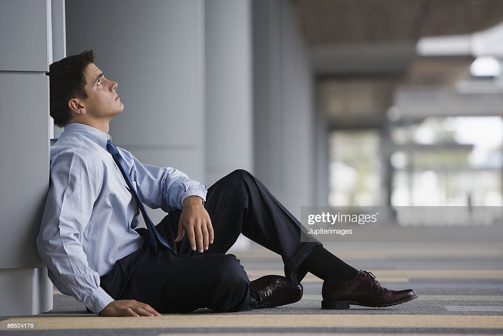Overwhelmed man sitting on floor : Stock Photo