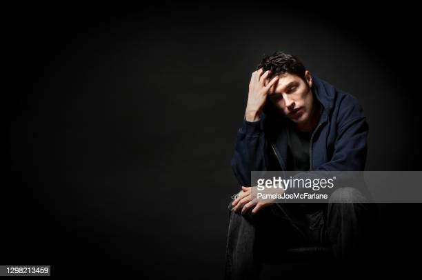 overwhelmed young man sitting with eyes closed - suicide stock pictures, royalty-free photos & images
