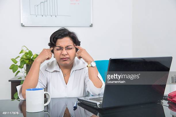 Overworked and stressed out Indian business woman working