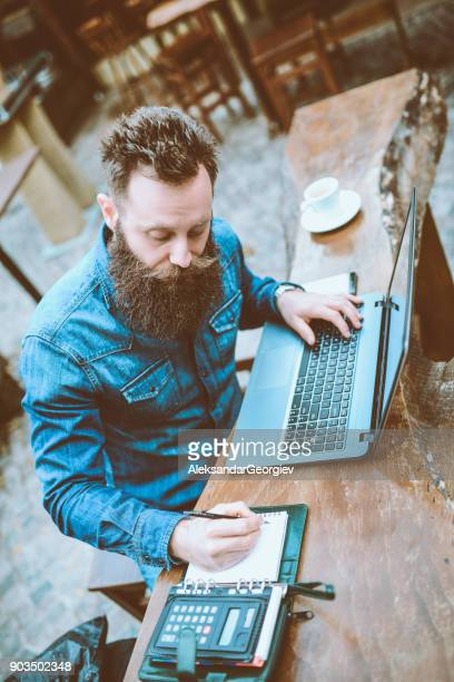 overworked bearded hipster freelancer working at his favorite cafe - fun calculator stock photos and pictures