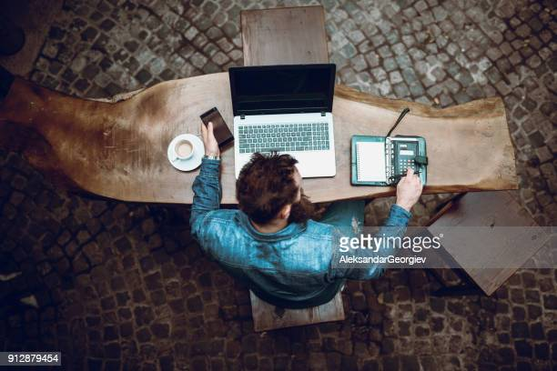 overworked bearded hipster freelancer working at his favorite coffee - fun calculator stock photos and pictures